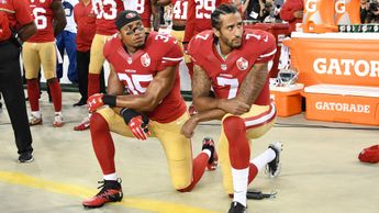 Colin Kaepernick (r) and Eric Reid, then of the 49ers, protest during last season