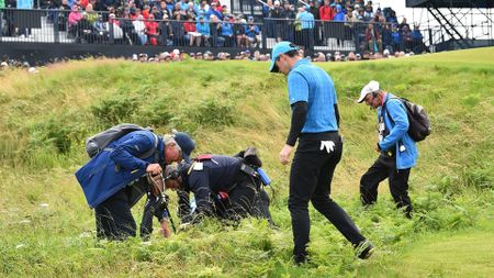 Rory McIlroy looks for his ball on the opening hole