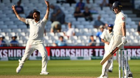 India's Jasprit Bumrah (L) celebrates as England's Chris Woakes loses his wicket for four