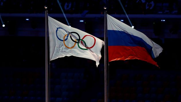 The Olympic flag flies next to the Russia flag