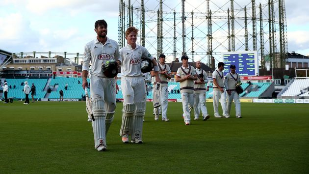 Ben Foakes and Ollie Pope of Surrey leave the field after making the final runs