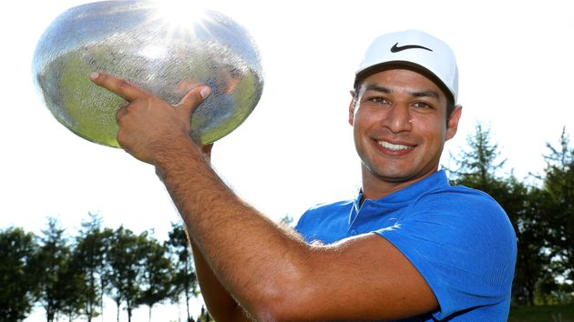 Julian Suri lifts the trophy after his four-shot success