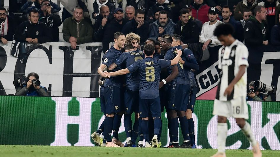 Manchester United players celebrate a late winner at Juventus