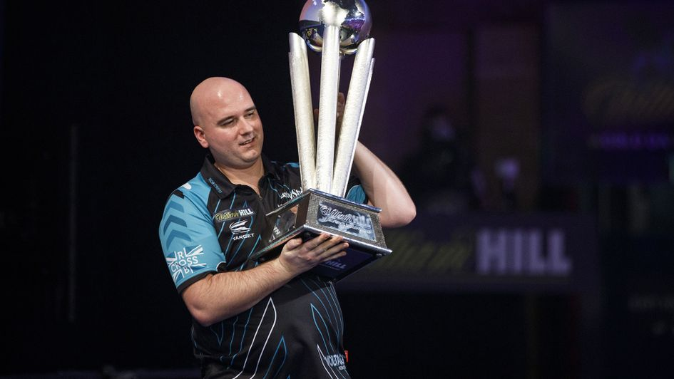 Rob Cross holds the world darts championship trophy aloft
