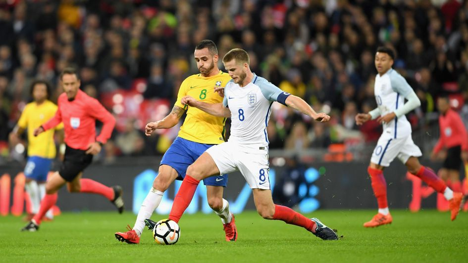 Renato Augusto and Eric Dier compete for the ball