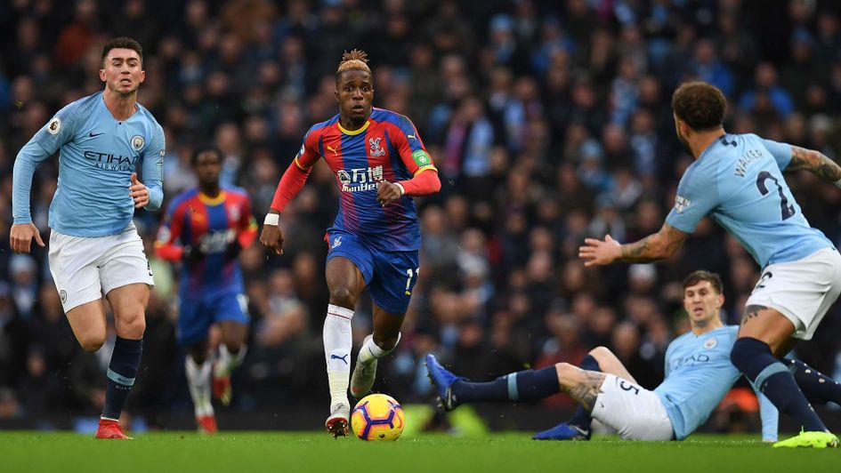 Wilfried Zaha takes on Manchester City's players at the Etihad