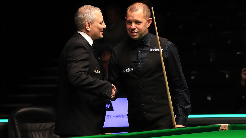 Barry Hawkins is congratulated by referee Brendan Moore