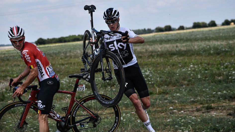 Chris Froome (right) carries his bicycle after falling on day one of Tour de France